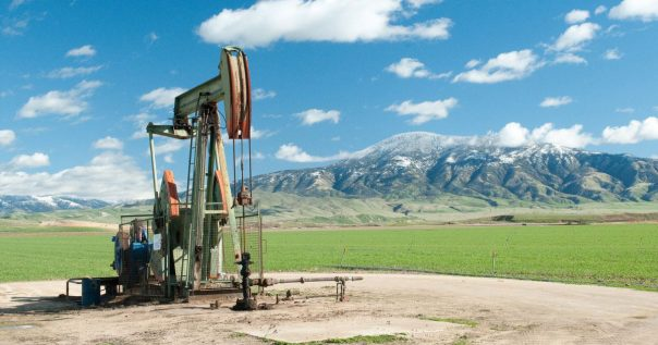 Pump jack in front of mountains.